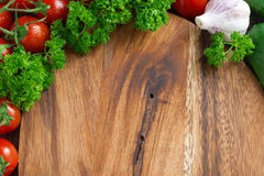 Wooden board background, fresh tomatoes and herbs Royalty Free Stock Photo