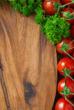 wooden board background, fresh tomatoes and herbs, vertical Stock Images
