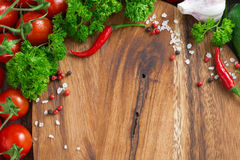 Wooden board background, fresh tomatoes, spices and herbs Royalty Free Stock Photography
