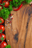 Wooden board background, fresh tomatoes, spices and herbs Stock Images