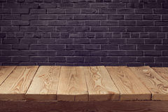 Wooden board background over black brick wall Royalty Free Stock Images