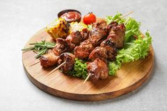 Wooden board with barbecued meat, garnish and sauce royalty free stock images