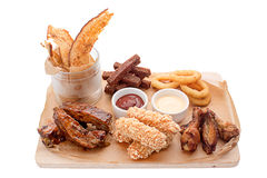 Wooden board beer snacks and sauces. On a wooden board beer snacks and sauces in a gravy boat. Cheese in batter, chicken wings, legs, onion, squid rings, bread stock images