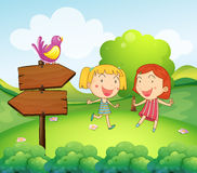 A wooden board with a bird beside the two young girls Stock Images