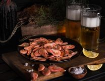 On a wooden board black plate with shrimps. Near glasses of light beer and lemon wedges stock photography