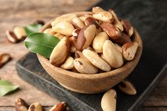 Wooden board with bowl of tasty Brazil nuts on table. Closeup stock photography