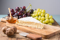 Wooden board with  brie cheese, grapes, nuts and honey Stock Photography