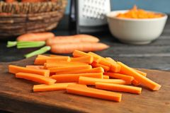Wooden board with carrot sticks. On table royalty free stock images