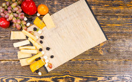 Wooden Board with Cheese and Fruit on Rustic Table Royalty Free Stock Photography