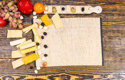 Wooden Board with Cheese and Fruit on Rustic Table Stock Photo