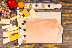 Wooden Board with Cheese and Fruit on Rustic Table Stock Photography