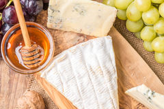Wooden board with cheeses, grapes, nuts and honey Royalty Free Stock Photo