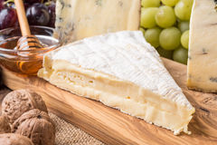 Wooden board with cheeses, grapes, nuts and honey Royalty Free Stock Photos
