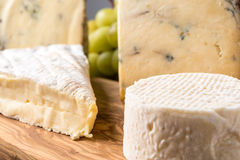 Wooden board with cheeses and grapes Royalty Free Stock Image