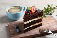Wooden board with chocolate sponge berry cake. And cup of coffee on grey background royalty free stock photos