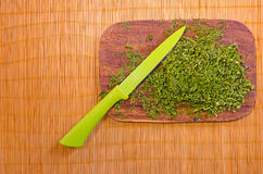 Wooden board with chopped herbs and a knife on a bamboo mat. Green chopped dill with a green knife on a wooden board Stock Photos