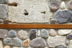 Wooden board concreted into a stone wall Stock Photos