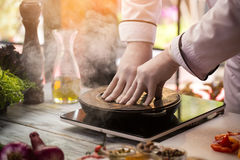 Wooden board covers frying pan. Stock Images