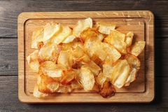 Wooden board with crispy potato chips on table Royalty Free Stock Photo