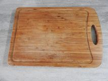 Wooden board for cutting foods on the table in the kitchen. royalty free stock photos