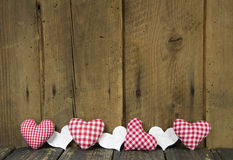 Wooden board decorated with checked hearts. Royalty Free Stock Photo