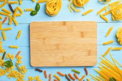Wooden board and different raw pasta on table. Top view Royalty Free Stock Photos