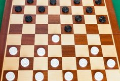 Wooden board with draughts on green table. Wooden checkered board with draughts on green baize table royalty free stock photos
