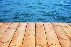 Wooden board empty floor in front of blue water sea background. Perspective brown wood over blur in sea - can be used for display or montage your products Stock Image