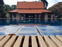 Wooden board empty table against of blurred swimming pool background stock photo