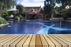Wooden board empty table against of blurred swimming pool background. Perspective brown wood over swimming pool. Stock Photo