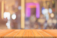 Wooden board empty table blur in restaurant background can be used for display or montage your products. Stock Photos