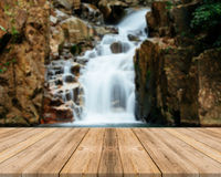 Wooden board empty table blur waterfall in forest - can be used for display or montage your products. Royalty Free Stock Photography