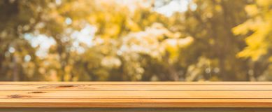 Wooden board empty table blurred background. Perspective brown wood table over blur trees forest background. Wooden board empty table blurred background royalty free stock photos