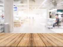 Wooden board empty table blurred shopping mall background. Perspective brown wooden table blur in department store background Stock Images
