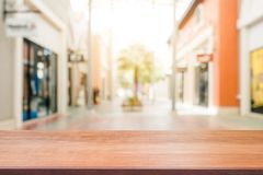 Wooden board empty table blurred shopping mall background. Perspective brown wooden table blur in department store background. Stock Photography