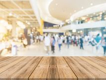 Wooden board empty table blurred shopping mall background. Royalty Free Stock Photo