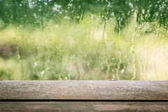 Wooden board empty table in front of blurred rainy window stock photography