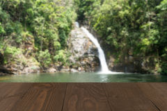 Wooden board empty table in front of blurred waterfall backgroun Stock Photo
