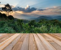 Wooden board empty table in front of sunset mountain landscape b Stock Images