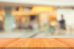 Wooden board empty table over blur in department store - can be used for display or montage your products. Royalty Free Stock Image