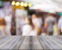 Wooden board empty table people shopping at market fair background. Stock Photo