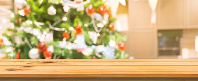 Wooden board empty table top blurred background. Perspective brown wooden table over blur christmas tree background. stock image