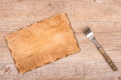 Wooden board with fork for a snack Royalty Free Stock Photos