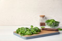 Wooden board with fresh green basil leaves on table. Space for text stock image