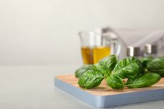 Wooden board with fresh green basil leaves on table. Space for text royalty free stock images