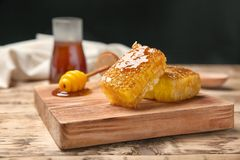 Wooden board with fresh honeycombs. On table Stock Photos
