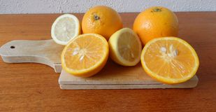 Wooden board with fresh oranges and lemons Stock Image