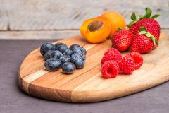 Wooden board with fresh organic fruit and berries Royalty Free Stock Image