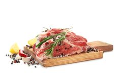 Wooden board with fresh raw meat and rosemary. On white background Stock Photo
