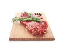 Wooden board with fresh raw meat and rosemary. On white background Royalty Free Stock Photo